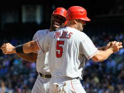 Albert Pujols (5) and Torii Hunter celebrate scoring on Mark Trumbo tiebreaking two-run single.