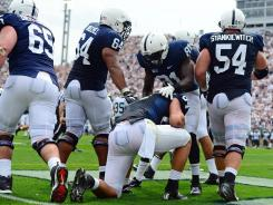 Penn State Nittany Lions center Miles Dieffenbach (65), John Urschel (64), Shawney Kersey (81) and Matt Stankiewitch (54) celebrate with Matt Lehman (84) after scoring a touchdown in the second quarter against the Ohio Bobcats at Beaver Stadium.