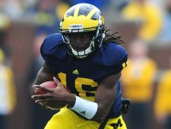 "Quarterback Denard Robinson says this season's Michigan team is ""like night and day. ""It's sunny over here. Last year was dark. It was nighttime. This year, I feel comfortable with the offense."""