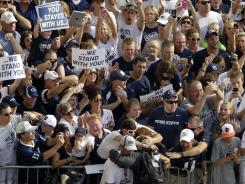 Penn State quarterback Matt McGloin, bottom center facing away, is hugged by fans as the Penn State football team arrives at Beaver Stadium for their season opener against Ohio.