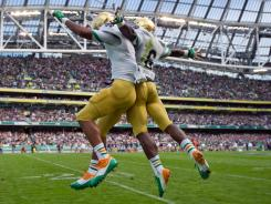 Fighting Irish running back George Atkinson III (4) celebrates with running back Theo Riddick (6) after Atkinson scored a touchdown in the first quarter against Navy.