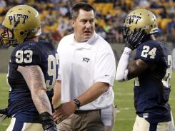 New Pitt head coach Paul Chryst, center, talks with defensive lineman Bryan Murphy (93) and defensive back Cullen Christian (24) as they come off the field in the second quarter.