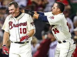 Braves second baseman Martin Prado, right, hits third baseman Chipper Jones with dirt to celebrate Jones' three-run homer that ended a 8-7 win vs. the Phillies.