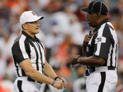 Locked out NFL referee Ed Hochuli talking with umpire Chad Brown during a preseason game in 2010.