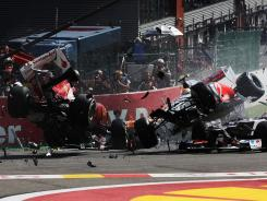 The cars of Fernando Alonso, left, and Lewis Hamilton collide and crash out at the first corner at the start of the Belgian Grand Prix on Sunday.