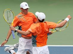 Mike Bryan, right, and Bob Bryan of the USA celebrate on their way to a third-round victory against Santiago Gonzalez of Mexico and Scott Lipsky of the USA on Monday at the U.S. Open.