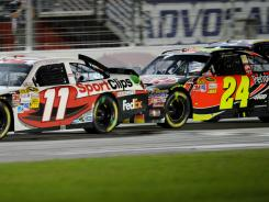 Denny Hamlin holds off Jeff Gordon on a green-white-checkered restart at Atlanta Motor Speedway on Sunday.