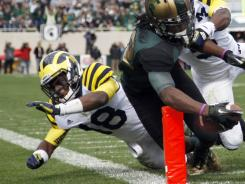 Michigan's Blake Countess, shown here making a tackle on Michigan State's Keshawn Martin in 2011, will miss the remainder of the season with a torn ACL.