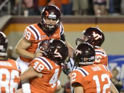 Virginia Tech kicker Cody Journell (89) hits the game winning field goal in overtime and is held up in celebration.