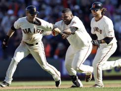 Marco Scutaro, left, is chased by Pablo Sandoval and Brandon Crawford after his game-winning hit in the 10th.
