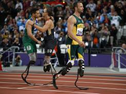 Brazil's Alan Fonteles Cardoso Oliveira, left, embraces Germany's David Behre, center, after winning the gold medal in the men's 200 meters at the Paralympics as silver medalist Oscar Pistorius of South Africa walks away.