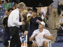 Andy Roddick gets the word from tournament referee Brian Earley at Aruther Ashe Stadium on Tuesday that his match with Juan Martin del Potro has been suspended.