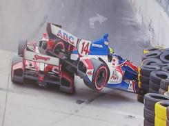 Justin Wilson, left, slides under Mike Conway's ABC Supply Car, which goes careening into the tire barrier during the Baltimore Grand Prix.