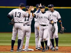 Yankees players celebrate their 6-4 win, which gave them the lead in the AL East.