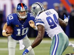Cowboys linebacker DeMarcus Ware brings down Giants quarterback Eli Manning for a sack during the first half.