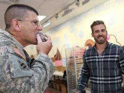 """U.S. Army Major Larry Ross takes a bite of a Royal Swedish Snowball as Red Wings star Henrik Zetterberg looks on. """"It tastes like a European s'more,"""" said Ross."""