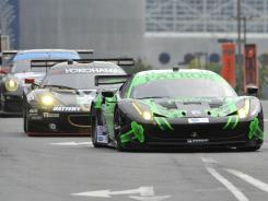 The No. 2 Patron Ferrari leads a group of American Le Mans Series cars through the streets of downtown Baltimore on Saturday. The ALMS and Rolex Grand-Am Sports Car Series are merging.