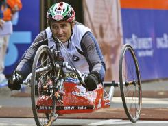 In this 2007 photo, Alex Zanardi, who lost both legs in a crash in a 2001 CART race in Germany, crosses the finish line in the men's handcycle category at the New York City Marathon.