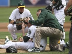 Athletics players and staff surround starting pitcher Brandon McCarthy after he was hit in the head by a line drive Wednesday.
