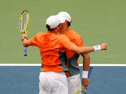 Bob Bryan, right, and Mike Bryan of the USA celebrate with a chest bump after defeating Aisam-Ul-Haq Qureshi of Pakistan and Jean-Julien Rojer of the Netherlands in a men's doubles semifinal Friday at the U.S. Open.