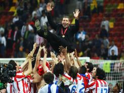 Atletico Madrid coach Diego Simeone is thrown in the air by his players following their 3-0 victory over Athletic Bilbao in the 2012 Europa League final, the club's second title in the three-year history of the competition