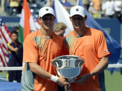 Mike and Bob Bryan show off the championship trophy after the men's doubles final against Leander Paes and Radek Stepanek.