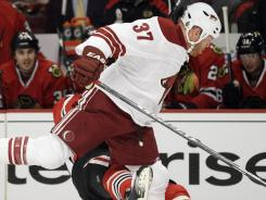 Raffi Torres hits Marian Hossa during the first round of the playoffs. Hossa left the ice on a stretcher.