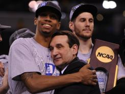 Duke coach Mike Krzyzewski hugs forward Lance Thomas after winning the 2010 men's basketball national championship.