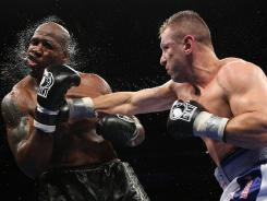 Tomasz Adamek, right, of Poland, lands a punch on Travis Walker during the fifth round of their heavyweight bout at the Prudential Center in Newark, N.J., Saturday. Adamek won by fifth round stoppage.
