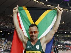 South Africa's Oscar Pistorius poses with a national flag after winning gold in the men's 400-meter dash.