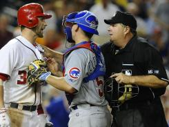 Nationals center fielder Bryce Harper is held back by home plate umpire Jerry Lane and Cubs catcher Steve Clevenger after an inside pitch Thursday.