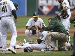 Oakland Athletics players and staff surround starting pitcher Brandon McCarthy (32) after being hit in the head on a line drive by Los Angeles Angels shortstop Erick Aybar.