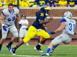 Air Force defensive lineman Nick DeJulio watches as Michigan quarterback Denard Robinson rushes past Air Force defensive back Brian Lindsay (31) for a 79-yard touchdown in the first quarter Saturday.