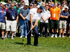 Phil Mickelson chips it out of the rough on the third hole during the third round of the BMW Championship.