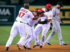 Howie Kendrick and Erick Aybar mob Alberto Callaspo after Collaspo's walk-off single in the ninth inning.