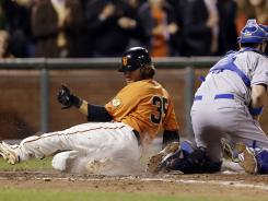 Brandon Crawford scores past Dodgers catcher A.J. Ellis on Marco Scutaro's tiebreaking single in the seventh inning.