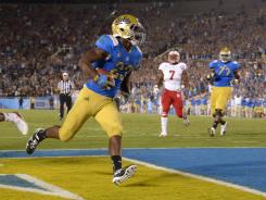 UCLA tailback Johnathan Franklin (23) celebrates after scoring on a 9-yard touchdown catch in the fourth quarter against Nebraska
