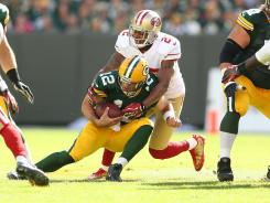 Packers quarterback Aaron Rodgers is sacked by the 49ers' Carlos Rogers during the NFL season opener at Lambeau Field.