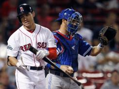 Red Sox center fielder Jacoby Ellsbury, left, turns away from Blue Jays catcher J.P. Arencibia after striking out in the eighth inning of a 9-2 Toronto win Saturday.