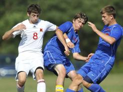 Bishop McCort's Jonathan Shearer, left, fights for the ball with Cambria Heights' Garrett Maslonik, middle, and Nathan Lieb during a high school soccer game in Benscreek, Pa., last week. High school teams across the country have lost top players to U.S. Soccer Academies.