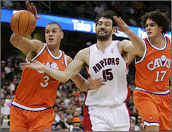 Cleveland's Sasha Pavlovic, left, and Anderson Varejao scramble for a loose ball with Toronto's Jorge Garbajosa.