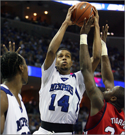 Memphis guard Chris Douglas Roberts goes to the basket against the defense of Houston's Jahmar Thorpe