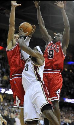 Chicago Bulls center Joakim Noah and forward Luol Deng (9) stop Cleveland Cavaliers forward LeBron James from scoring on the last play of the game as the Bulls beat the Cavs 86-85.