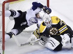 Boston Bruins goalie Tim Thomas, right, makes a save as an airborne Tampa Bay Lightning center Steven Stamkos ends up in the net.
