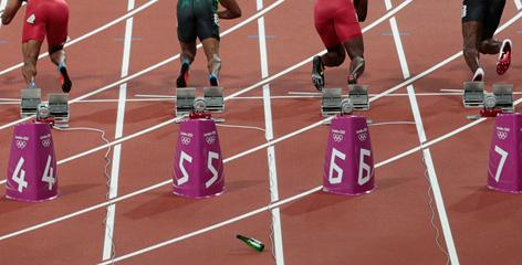 A bottle lands on the track just behind the participants in the 100-meter final on Sunday at the Olympics.