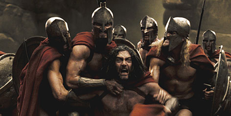 A Spartan captain is restrained by his soldiers in a scene from 300. The movie, about an ancient battle at Thermopylae, takes history and a graphic novel into account.