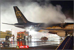 Firefighters battle a blaze onboard a UPS cargo plane, Feb. 8, 2006, at Philadelphia International Airport in Philadelphia. The National Transportation Safety Board is investigating if the lithium batteries that were among the cargo were responsible for the fire.