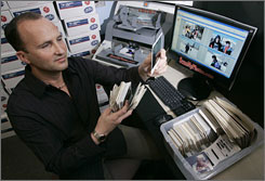 Mitch Goldstone uses a high-speed scanner to convert prints to digital files at 30 Minute Photos in Irvine, Calif.