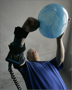 Stroke victim Bill Dressel demonstrates his elbow brace, which helped him regain arm mobility after he had a stroke, in his house in Littleton, Mass.