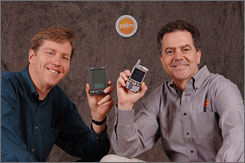 Palm founder Jeff Hawkins (left, with original Pilot connected organizer) and Ed Colligan, now president and chief executive officer (right, with Treo 650 smartphone).